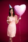 Mujer que sostiene el globo y el buñuelo en forma de corazón con la vela Foto de archivo