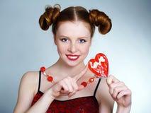 Mujer que sostiene el Lollipop en forma de corazón Imagen de archivo