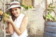 Mujer que sostiene el manojo de uvas fotografía de archivo