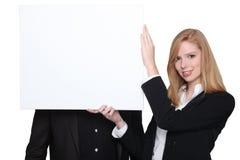 Mujer que sostiene el panel en blanco de la publicidad Fotografía de archivo libre de regalías