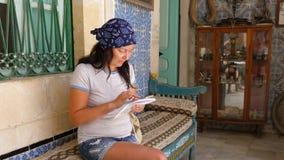 Mujer que sostiene el papel disponible y que usa el teléfono móvil en el sofá en interior del sitio almacen de video