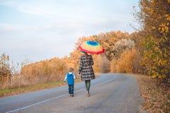 Mujer que sostiene el paraguas que camina con el muchacho el otoño Imagen de archivo libre de regalías