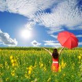 Mujer que sostiene el paraguas rojo en campo de flor y cielo amarillos del sol Imagen de archivo