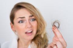 Mujer que sostiene el pelo de la pérdida Imagenes de archivo