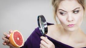 Mujer que sostiene el pomelo magniferlooking fotos de archivo