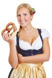 Mujer que sostiene el pretzel en dirndl Fotos de archivo