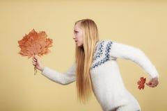 Mujer que sostiene el ramo hecho de las hojas de otoño imagen de archivo libre de regalías