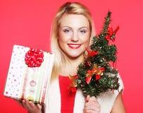 Mujer que sostiene el regalo y el árbol Fotografía de archivo libre de regalías