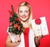 Mujer que sostiene el regalo y el árbol Imágenes de archivo libres de regalías
