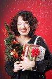 Mujer que sostiene el regalo y el árbol Imagen de archivo