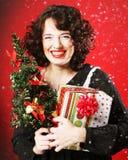 Mujer que sostiene el regalo y el árbol Imagen de archivo libre de regalías
