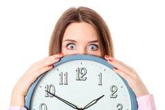 Mujer que sostiene el reloj con los ojos que se preguntan Fotografía de archivo