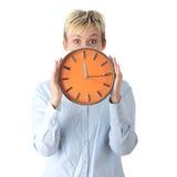 Mujer que sostiene el reloj de alarma grande Imagenes de archivo