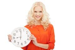 Mujer que sostiene el reloj grande Fotos de archivo libres de regalías