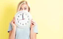 Mujer que sostiene el reloj que muestra casi 12 Foto de archivo libre de regalías