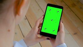 Mujer que sostiene el smartphone negro con la pantalla verde en blanco - concepto clave de la croma almacen de metraje de vídeo