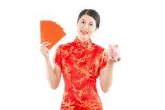 Mujer que sostiene el sobre y la hucha rojos Foto de archivo