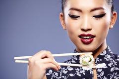 Mujer que sostiene el sushi con los palillos Fotografía de archivo