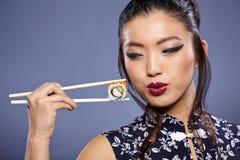 Mujer que sostiene el sushi con los palillos Foto de archivo