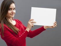 Mujer que sostiene el tablero o el papel en blanco para un anuncio Imágenes de archivo libres de regalías
