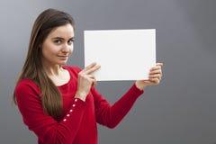 Mujer que sostiene el tablero o el papel en blanco para un anuncio Foto de archivo