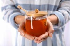 Mujer que sostiene el tarro de cristal con la miel dulce fresca Imágenes de archivo libres de regalías