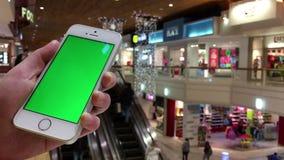 Mujer que sostiene el teléfono celular verde de la pantalla al lado de la escalera móvil almacen de metraje de vídeo