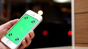 Mujer que sostiene el teléfono celular verde de la pantalla en fondo de iluminación borroso hermoso metrajes