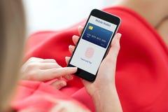Mujer que sostiene el teléfono con la huella dactilar para las compras en línea imágenes de archivo libres de regalías