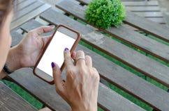 Mujer que sostiene el teléfono elegante imagen de archivo libre de regalías