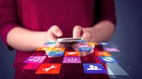 Mujer que sostiene el teléfono elegante con los iconos coloridos del uso Foto de archivo libre de regalías