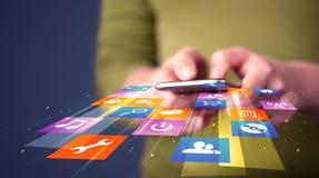 Mujer que sostiene el teléfono elegante con los iconos coloridos del uso Imagenes de archivo