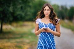 Mujer que sostiene el teléfono elegante Imagen cosechada de los jóvenes bastante de moda Foto de archivo