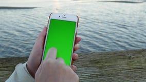 Mujer que sostiene el teléfono elegante móvil de la pantalla de visualización verde metrajes