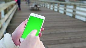 Mujer que sostiene el teléfono elegante móvil de la pantalla de visualización verde almacen de metraje de vídeo