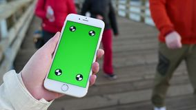 Mujer que sostiene el teléfono elegante móvil de la pantalla de visualización verde con gesto del finger almacen de video