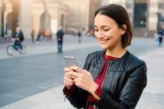 Mujer que sostiene el teléfono elegante para la comunicación urbana de la ciudad Fotos de archivo libres de regalías