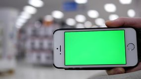 Mujer que sostiene el teléfono móvil de la pantalla verde en fondo de iluminación borroso hermoso dentro de la tienda de Walmart