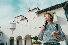 Mujer que sostiene el teléfono mientras que visita el nuevo lugar imágenes de archivo libres de regalías