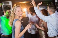 Mujer que sostiene el vidrio de champán mientras que baila con los amigos Fotografía de archivo libre de regalías