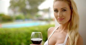 Mujer que sostiene el vidrio de vino rojo al aire libre cerca de piscina