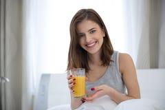 Mujer que sostiene el zumo de naranja en la cama Imágenes de archivo libres de regalías