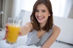 Mujer que sostiene el zumo de naranja en la cama Fotografía de archivo libre de regalías