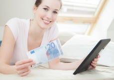Mujer que sostiene 20 euro y la tableta Fotos de archivo libres de regalías
