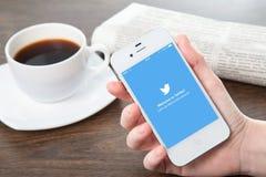 Mujer que sostiene iPhone con Twitter en la pantalla Fotografía de archivo