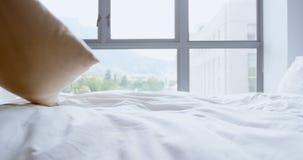 Mujer que sostiene la almohada en el dormitorio 4k almacen de video