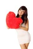 Mujer que sostiene la almohada en forma de corazón Imagen de archivo
