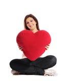 Mujer que sostiene la almohadilla en forma de corazón Fotos de archivo