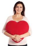 Mujer que sostiene la almohadilla en forma de corazón Imágenes de archivo libres de regalías