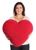 Mujer que sostiene la almohadilla en forma de corazón Imagen de archivo